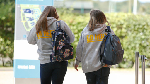 Two female students walking down path away from camera