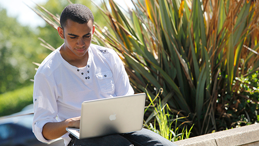 a student sits on the grass with his laptop