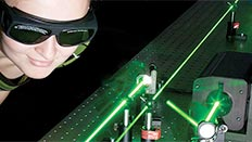 Female student next to a laser beam.