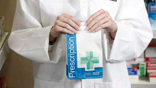 Pharmacist putting medicine in bag