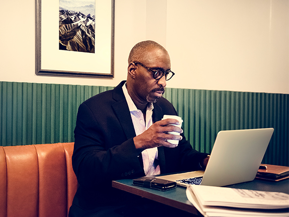 Man on laptop in restaurant