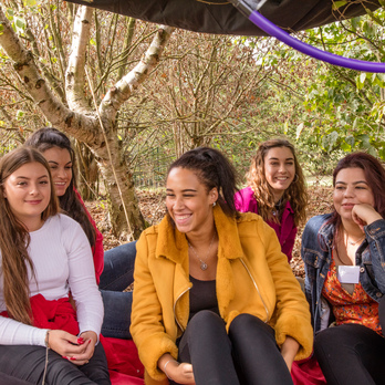 a group of six female university students sitting together in a some woodland beneath a canopy.