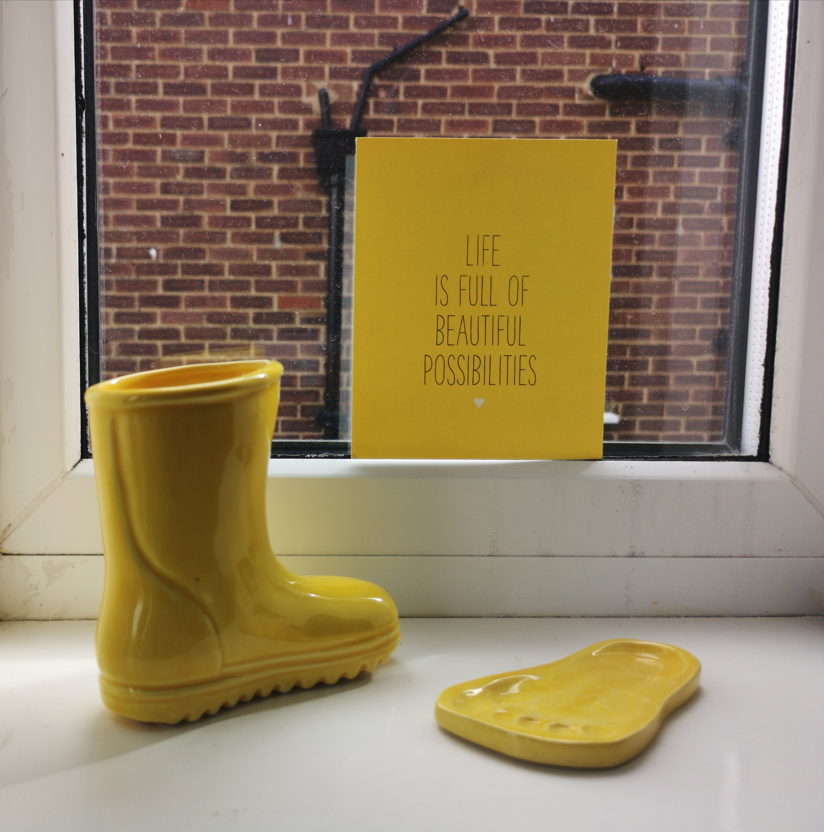 Yellow themed objects placed on a windowsill. Yellow Ceramic boot and footprint. And a yellow poster reading 'Life is full of beautiful possibilities.