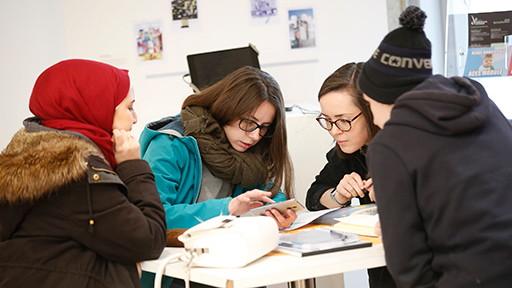 a group of students look at a mobile phone