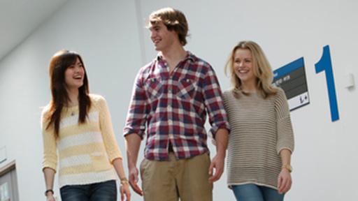 three people walk down a corridor