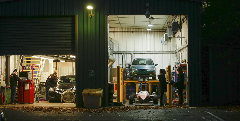 Students outside car garage at night