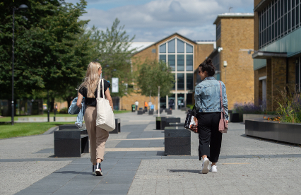 Two female students walking outside in sunshine
