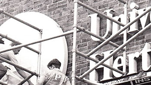 workers put up a University of Hertfordshire sign