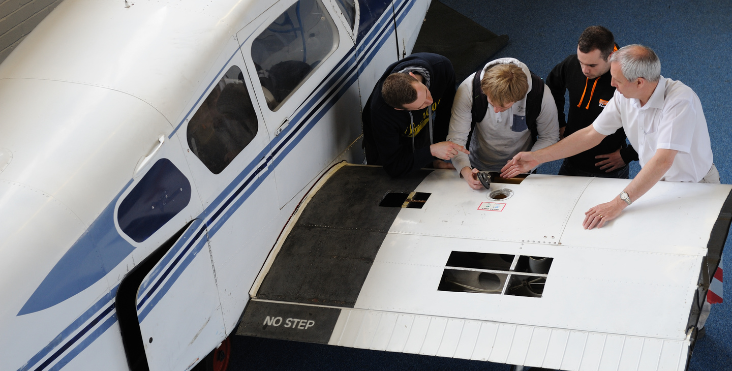 Students working on aeroplane wing