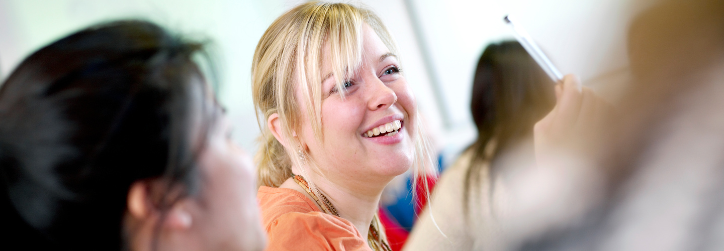 Blonde female student laughing in classroom