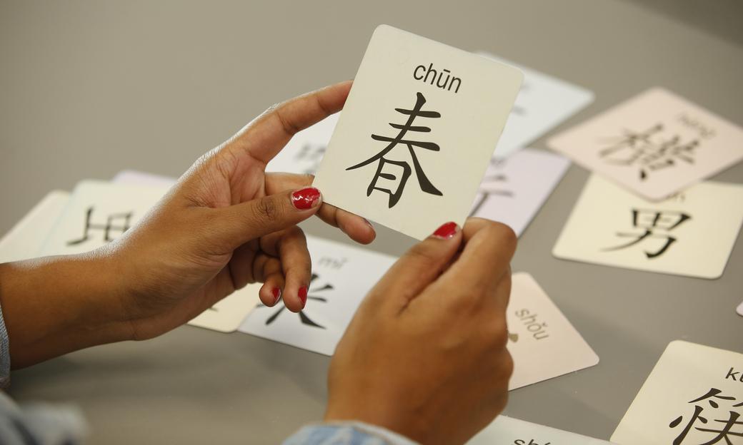 Student holding language card