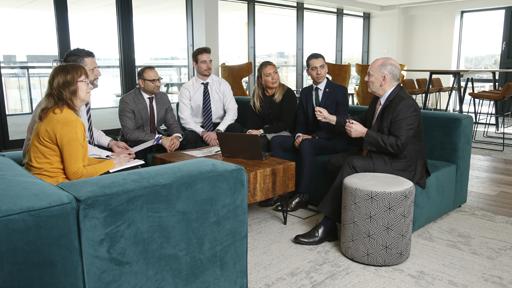 Men and women having meeting on sofas