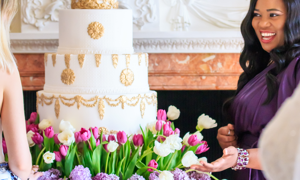 Tees Bakery owner standing next to a wedding cake