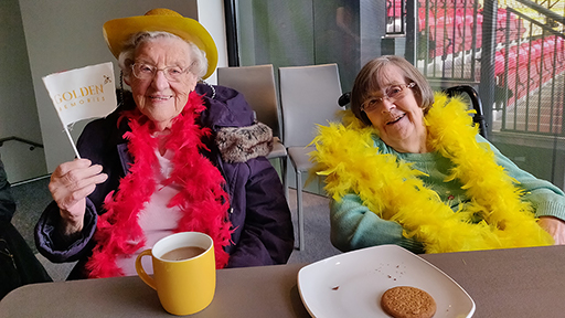 Two mature ladies smile as they enjoy a cuppa and biscuits. One waves a small flag which reads 'Golden Memories'