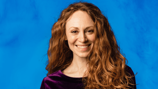 a person with long auburn hair smiles against a blue backdrop