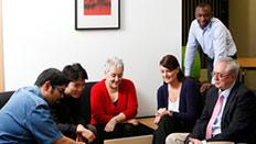 professionals gathering around a laptop