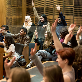 Students raising hands in law court