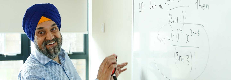 Male academic writing on whiteboard