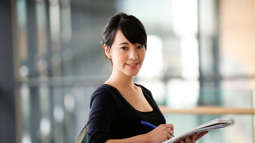 Female mature student holding pen and paper