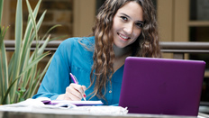 A smiling student with a laptop