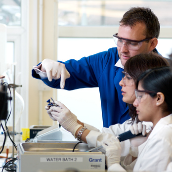 A lecturer is teaching students in a lab