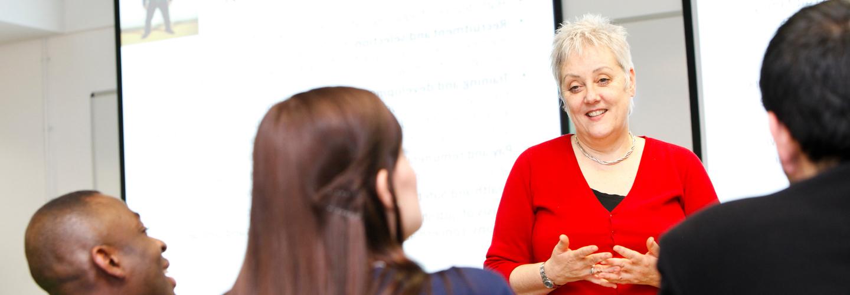 Female academic speaking to students in seminar