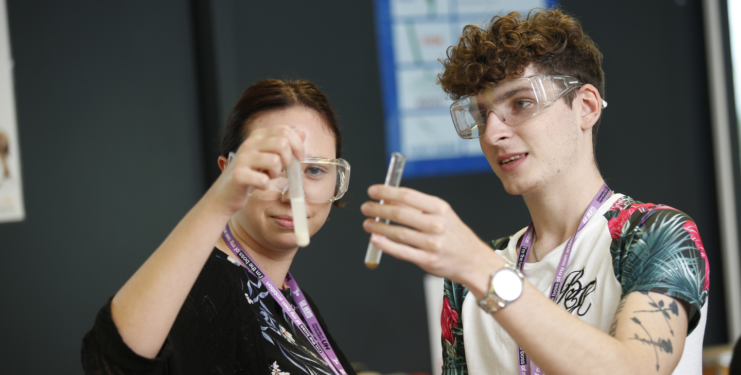 Male and female student looking at vials