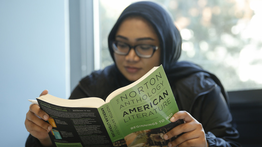 Female student reading American literature book