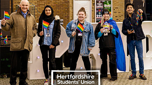 Vice Chancellor, Quintin McKellar waves a rainbow flag with members of the LGBT+ Society at Herts
