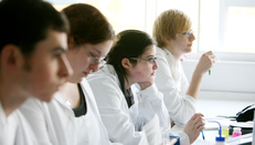 Students wearing lab coats in a lecture